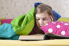 Girl reading in bed Stock Images