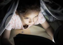 A girl reading on the bed Stock Images