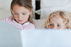 Girl reading a bed time story for her brother. Girl reading a bed time story for her little brother Royalty Free Stock Image