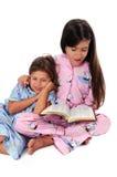 Girl Reading Bedtime Story to Sister. Girl reading the Bible as a bedtime story to sister Royalty Free Stock Photos