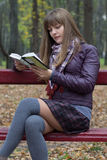 Girl reading on a bench Royalty Free Stock Image
