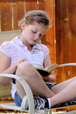 Girl reading bible. A little young girl sitting in a chair reading her bible. Shallow depth of field Stock Images