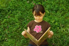 Girl reading a book. Little girl reading a book outside Royalty Free Stock Image