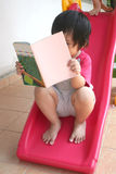 Girl reading book. On the slide Royalty Free Stock Photo