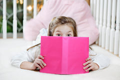 Girl reading book. Young girl lying on the floor reading, peeking over her book royalty free stock photo