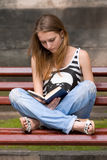 Girl reading book. Attractive girl is reading book in the city on the bench Royalty Free Stock Photo
