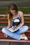 Girl reading book. Attractive girl is reading book in the city on the bench Royalty Free Stock Photography