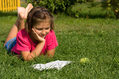 Girl reading a book. Lying on the grass Stock Image