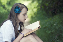Girl reading a book. In park Stock Images