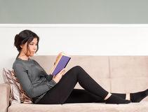 Girl Reading Book. Horizontal photo of a young female student, reading a book, while she is sitting on a couch and resting. The girl spends her free time / Royalty Free Stock Image