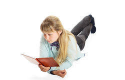 Girl  reading a book. Cute blond girl lying down reading a book Royalty Free Stock Photography
