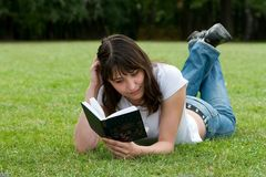 Girl reading a book. Cute girl reading a book on meadow stock photos