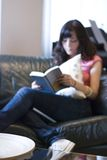 Girl reading book. A girl reading a book in front of a table royalty free stock images