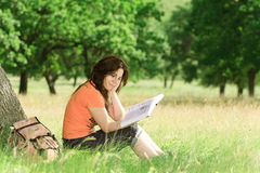 Girl reading a book. Girl reading book on green meadow Stock Images