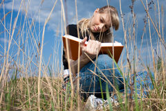 Girl reading the book. Girl reading book and sitting outdoor with sky in background Royalty Free Stock Photography