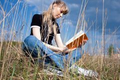 Girl reading the book. Girl reading book and sitting outdoor with sky in background Royalty Free Stock Image