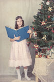 Girl reading book around Christmas tree Royalty Free Stock Photo