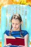 Girl reading a book in autumn garden royalty free stock photography