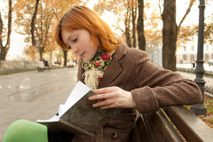 Girl reading book in autumn park Royalty Free Stock Photos