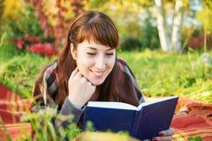 Girl reading a book in autumn park Stock Photos