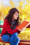 Girl reading a book in autumn park Stock Photo