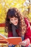 Girl reading a book in autumn park Royalty Free Stock Photos