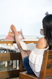 Girl reading book on the balcony with seaside view royalty free stock photo
