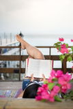 Girl reading book on the balcony with seaside view Stock Image