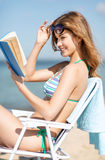 Girl reading book on the beach chair Royalty Free Stock Images