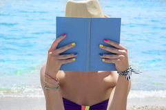 Girl reading a book on the beach Royalty Free Stock Images