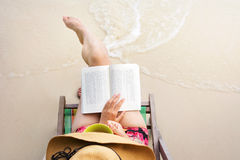 Girl reading a book at the beach Royalty Free Stock Images