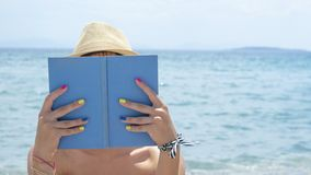 Girl reading a book on the beach wearing straw hat Stock Images
