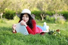 Girl reading the book.  beautiful young woman with book lying on the grass. Outdoor. Sunny day. Girl reading the book. beautiful young woman with book lying on Royalty Free Stock Photography