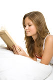 Girl reading book in bed Stock Photos