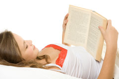 Girl reading book in bed Royalty Free Stock Photo