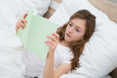 Girl Reading Book In Bedroom Royalty Free Stock Photos