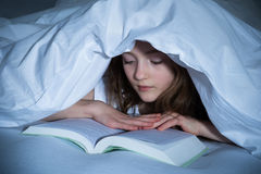 Girl Reading Book In Bedroom Royalty Free Stock Image