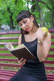 A girl is reading a book. A girl on a bench with an apple in her hand reading a book Stock Image
