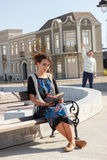 Girl reading a book on a bench while the man in the background w stock photography