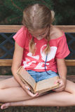 Girl reading a book on a bench Stock Photo