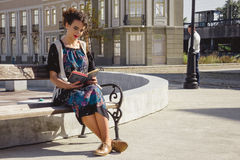 Girl reading book on bench in town while  man is stocking  in th Stock Images