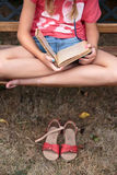 Girl reading a book on a bench Royalty Free Stock Images