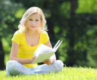 Girl reading the book. Blonde beautiful young woman with book sitting on the grass. Outdoor. Sunny day. Looking at the camera stock images