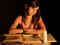 Girl reading book with candle. Black background Royalty Free Stock Images