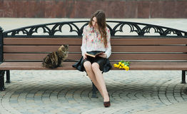 Girl reading a book with a cat on a bench in the city.  Royalty Free Stock Images