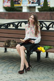 Girl reading a book with a cat on a bench in the city.  Stock Photo