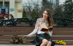 Girl reading a book with a cat on a bench in the city.  Royalty Free Stock Photos