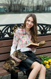 Girl reading a book with a cat on a bench in the city.  Stock Image