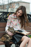 Girl reading a book with a cat on a bench in the city.  Royalty Free Stock Photo