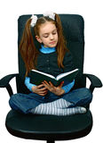 Girl reading a book in chair Stock Photography
